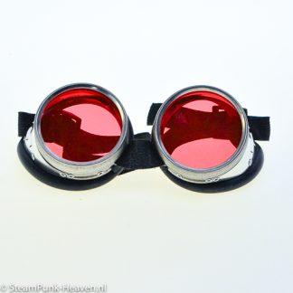 Steampunk Schweissbrille 4 ist silberfarben, dekoriert mit roten Gläsern und gefertigt aus Metall. Diese Schweissbrille ist an der Nase mit einem schwarzen Lederband versehen. Ausserdem ist die Brille ausgestattet mit einem Gummizug, sodass sie auf jeden Hut und jeden Kopf passt.